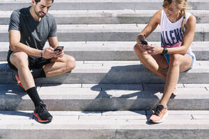 Couple using smart phones while sitting on steps in city during sunny day - JCMF01154