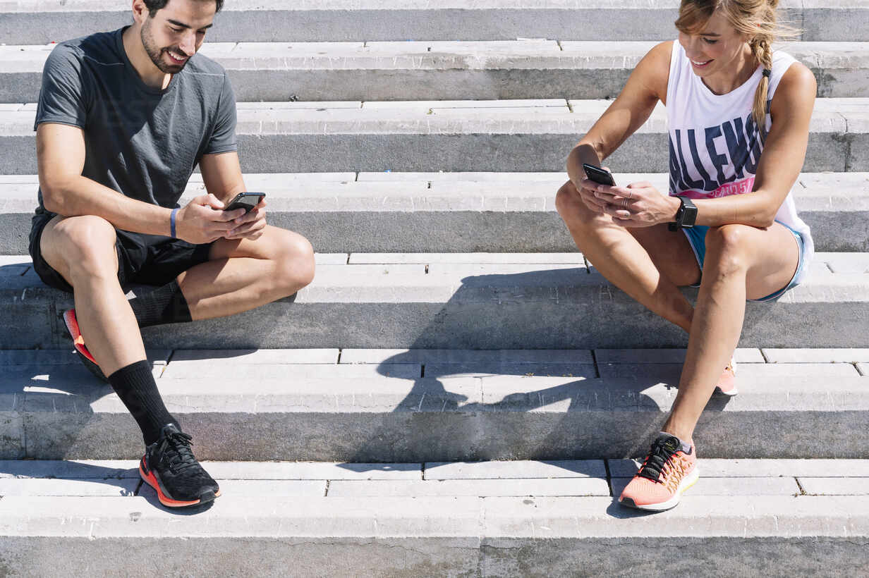 Couple using smart phones while sitting on steps in city during sunny day - JCMF01154 - Jose Luis CARRASCOSA/Westend61