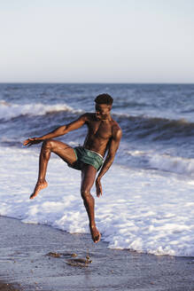 Shirtless African young man jumping at shore against clear sky - LJF01708
