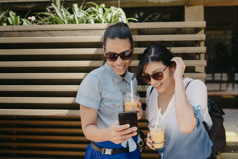 Female friends wearing sunglasses looking photograph over smart phone in city - DSIF00069
