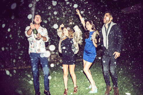 Young man opening champagne while friends dancing outdoors in party at night - EHF00693