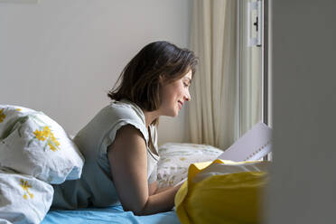 Smiling woman reading from note pad in bedroom - AFVF06865