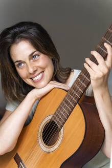 Smiling woman with guitar in bedroom - AFVF06874