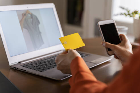 Cropped image of businesswoman with credit card using smart phone while purchasing online at home - AFVF06889