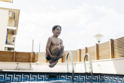 Excited boy jumping in pool against sky during summer - JRFF04676