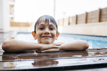 Smiling boy leaning on poolside - JRFF04685