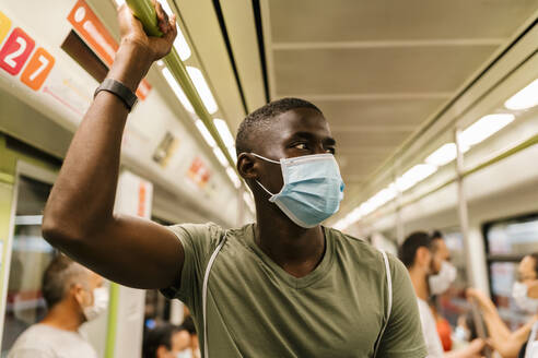 Young man wearing mask looking away while standing in subway train - EGAF00609