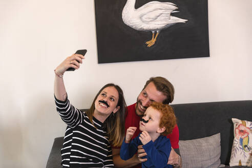 Woman wearing artificial mustache taking selfie with family on sofa at home - EIF00160