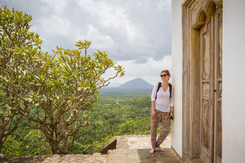 Female traveler with backpack looking away while leaning on wall of ancient oriental temple against cloudy sky in Sri Lanka - ADSF07242