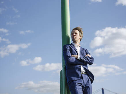 Thoughtful businessman with arms crossed standing by pole against sky during sunny day - GUSF04293