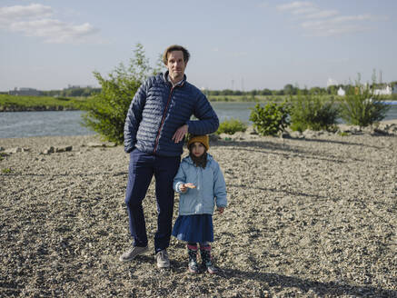 Father with daughter standing on land against Rhine river during sunny day - GUSF04317