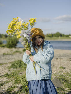 Cute girl holding flowers while standing on land against sky during sunny day - GUSF04341