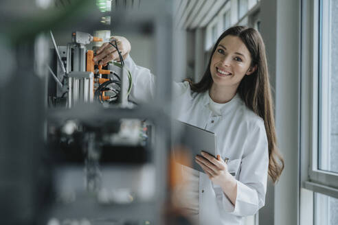 Smiling female scientist holding digital tablet inventing machinery in factory - MFF05924