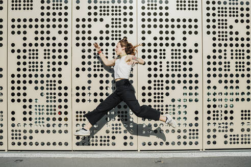 Woman running against wall with holes - MEUF01697