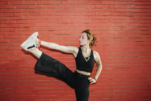 Beautiful woman stretching leg against red wall - MEUF01715