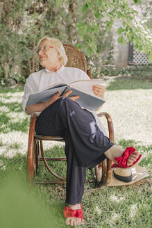 Senior woman holding book looking away while relaxing on chair in yard - ERRF04119