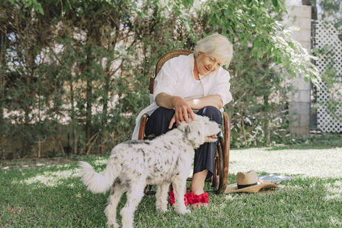 Smiling senior woman playing with dog while sitting on chair in yard - ERRF04122