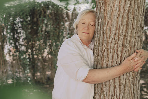 Senior woman with eyes closed embracing tree trunk while standing in yard - ERRF04125