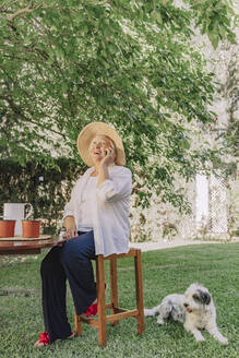 Cheerful senior woman talking over smart phone while sitting on stool by dog in yard - ERRF04128