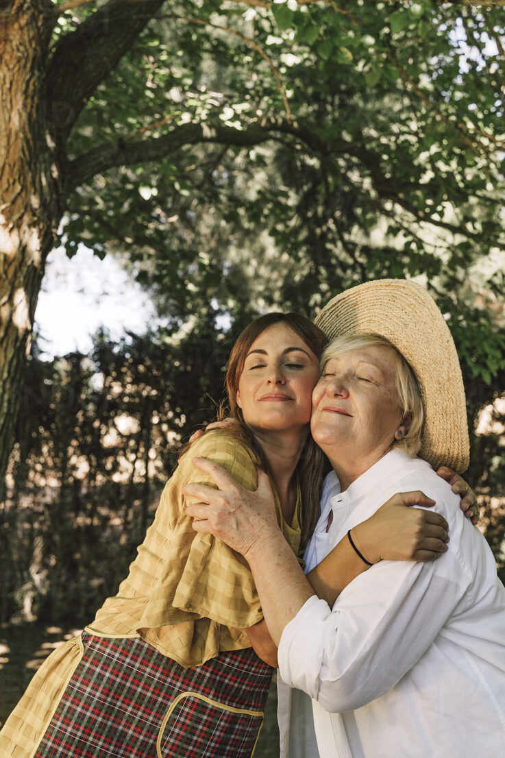Mother and daughter with eyes closed embracing in yard - ERRF04131 - Eloisa Ramos/Westend61