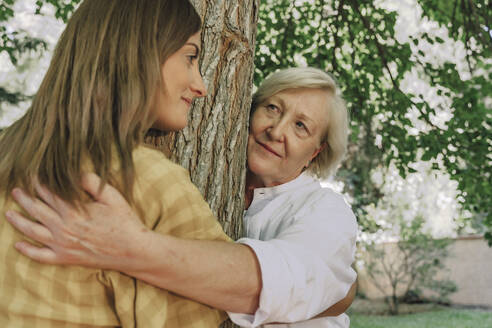 Mother looking at daughter while embracing tree trunk with her in yard - ERRF04152