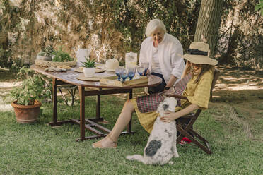 Mother and daughter with dog relaxing in picnic at yard - ERRF04161