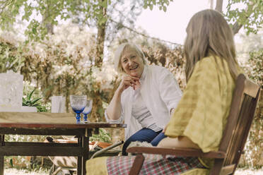 Happy senior woman talking with daughter while sitting at table in yard - ERRF04164