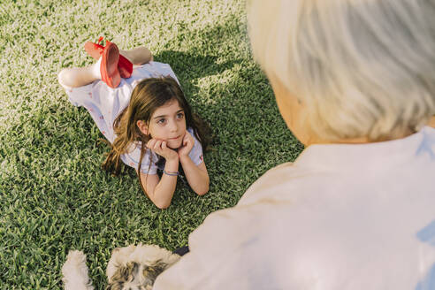 Cute girl with hands on chin looking at grandmother while lying over grassy land in yard - ERRF04179