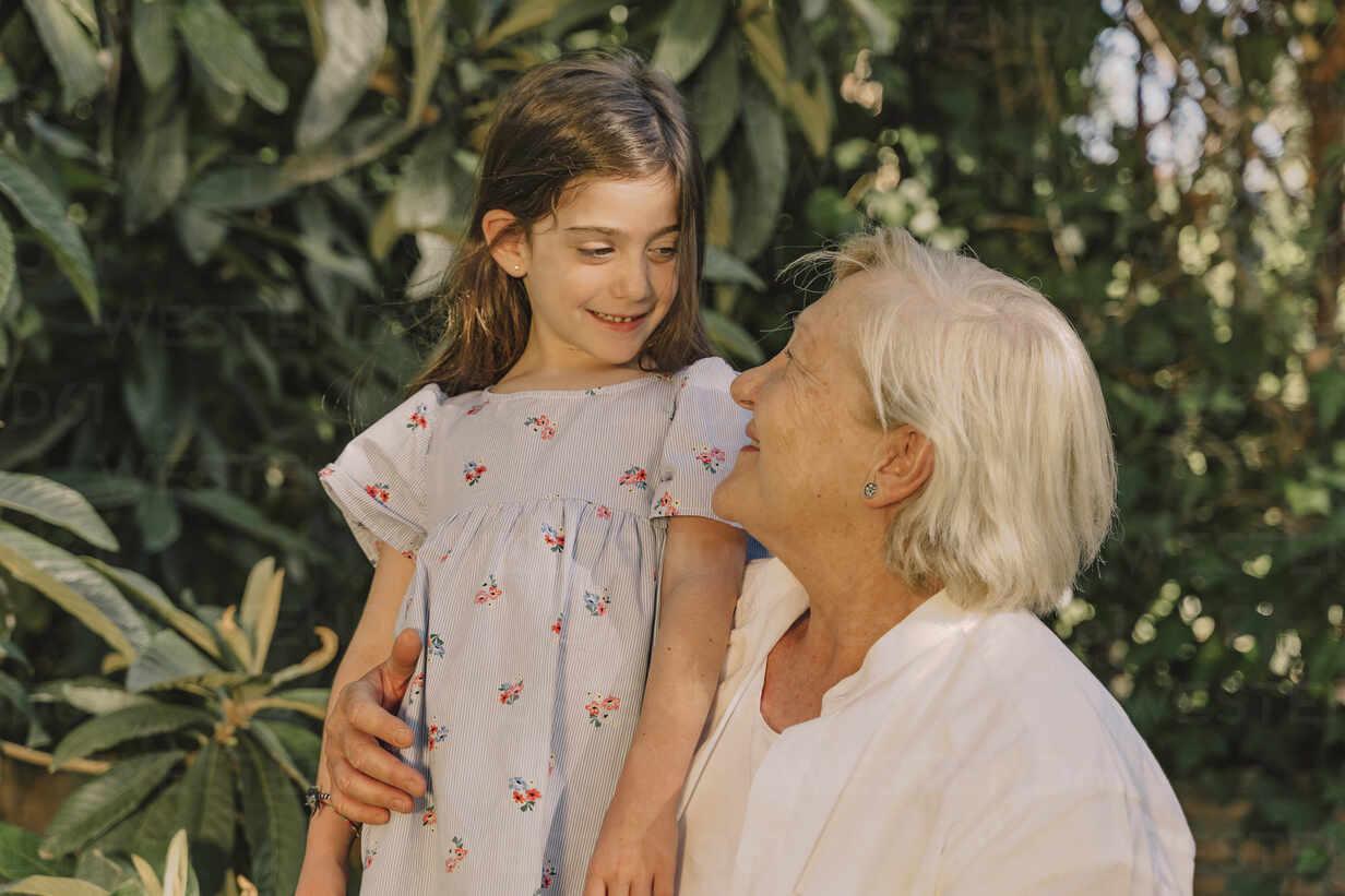 Smiling senior woman looking at cute granddaughter against plants in yard - ERRF04182 - Eloisa Ramos/Westend61
