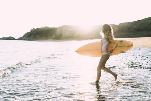 Young woman with surfboard running in sea against clear sky during sunset - MTBF00579