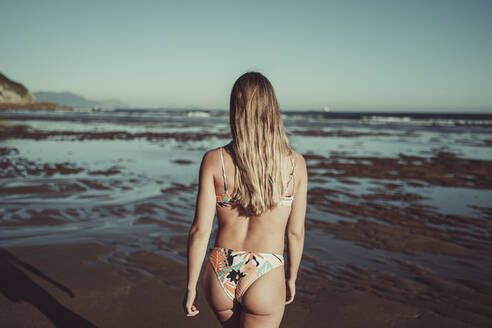 Young woman wearing bikini walking at beach against clear sky during sunset - MTBF00588