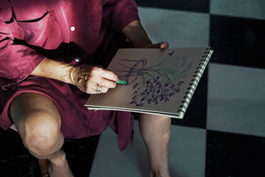 Close-up of senior woman drawing in book with crayon at home - ERRF04195