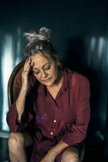 Sad senior woman with head in hand sitting on chair at home - ERRF04207