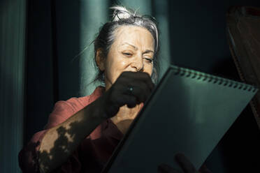 Close-up of senior woman drawing in book while against curtain at home - ERRF04216