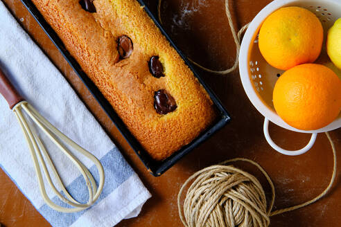 Top view of freshly baked sponge chocolate cake and ripe oranges placed on table near whisk and thread in kitchen - ADSF08348
