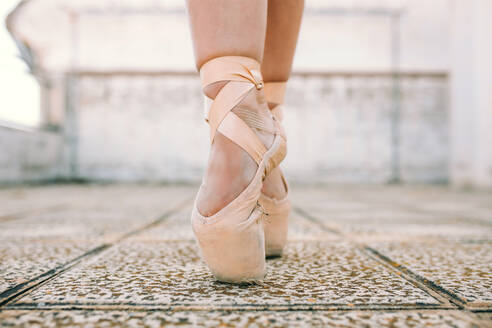 Crop female dancer wearing pointe shoes standing on tiptoes on weathered stone ground and demonstrating dancing position - ADSF08531