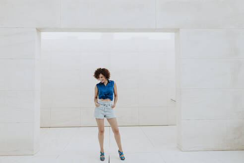 Smiling woman with curly hair standing against tiled wall - GMLF00374