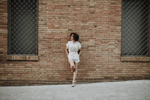 Mid adult woman with curly hair leaning on brick wall in city - GMLF00386