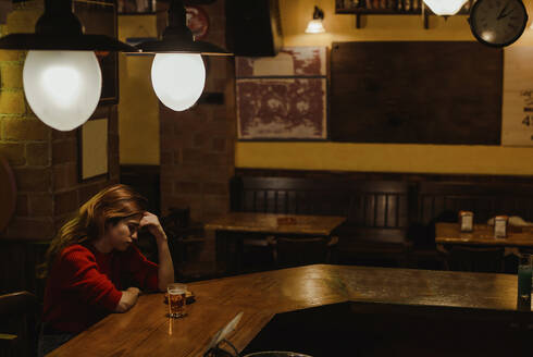 Sad woman with beer glass on bar counter sitting in restaurant - LJF01722