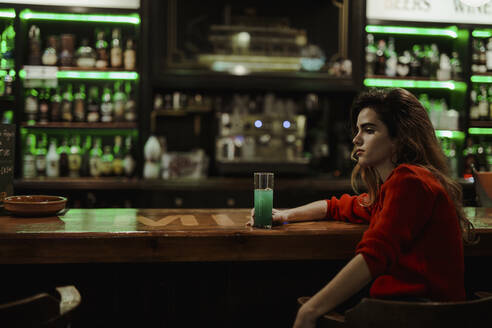Thoughtful woman with drink on bar counter sitting in restaurant - LJF01728