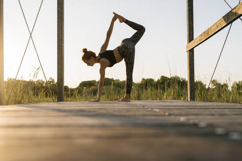 Young athlete practicing half moon pose on pier at countryside - EGAF00619