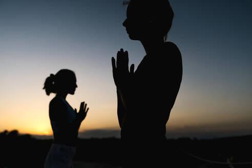 Silhouette women in prayer position during sunset - EGAF00625