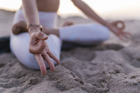 Close-up of young woman meditating on sand at beach - EGAF00637