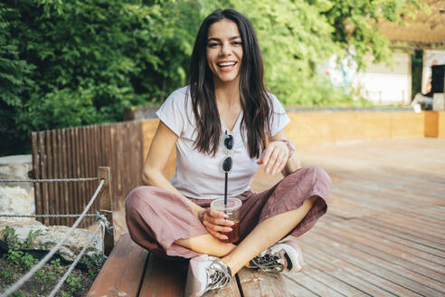 Young cheerful woman holding coffee while sitting on bench in park - OYF00179