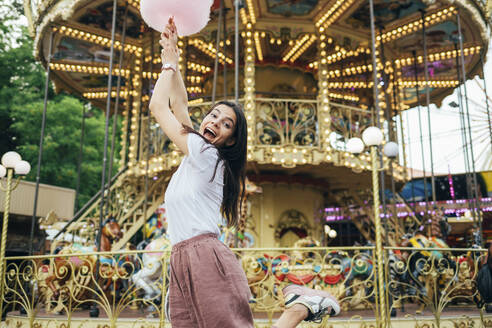 Young woman holding cotton candy screaming while dancing against carousel in amusement park - OYF00185