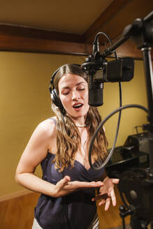 Singer with headphones at microphone in recording studio - LJF01734