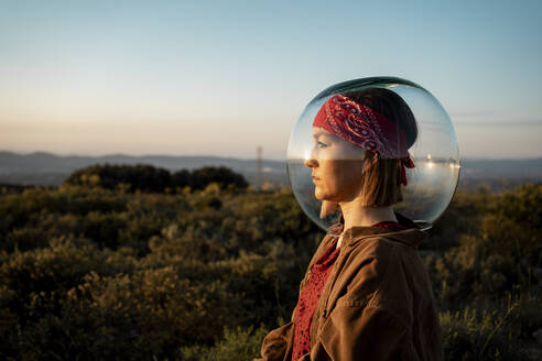Woman with a fish bowl on her head in the countryside - RCPF00281
