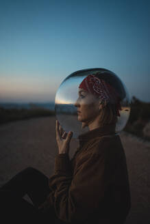 Woman with a fish bowl on her head sitting on a road in the countryside at dusk - RCPF00287
