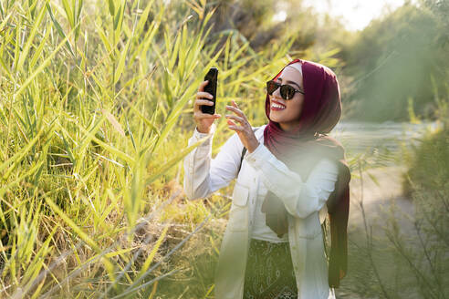 Smiling young tourist woman wearing Hijab taking a selfie - MPPF00959