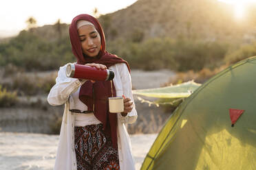 Smiling young tourist woman wearing Hijab at a tent pouring tea into mug - MPPF00983